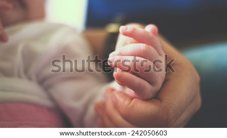 hand of the the sleeping baby in the hand of father close-up - stock photo