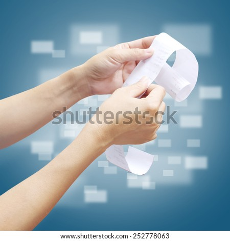 hand of woman checking a long  receipt - stock photo