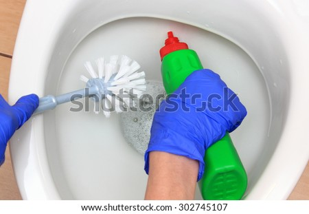 Hand of woman in blue glove cleaning toilet bowl using brush and detergent, concept for house cleaning and household duties - stock photo