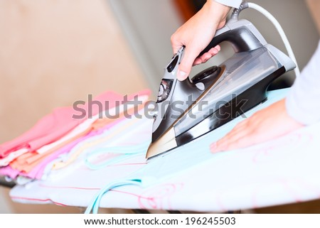 hand of woman ironing clothes on the table close up - stock photo