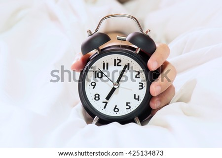 Hand of woman  lying in bed turning off an alarm clock in the morning - stock photo