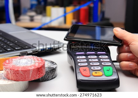 Hand of woman paying with NFC technology on mobile phone in an electrical shop, credit card reader, payment terminal, finance concept - stock photo