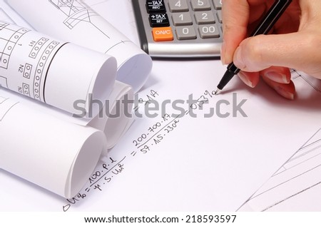 Hand of woman performing mathematical calculations for project, rolled electrical diagrams, drawings for the projects engineer jobs - stock photo