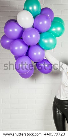 Hand of woman with colored balloons - stock photo