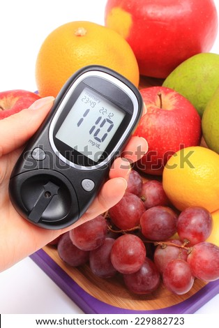 Hand of woman with glucose meter and fresh natural fruits on cutting board, concept for healthy eating and diabetes - stock photo