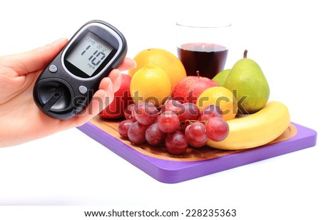 Hand of woman with glucose meter and fresh natural fruits on cutting board in background, concept for healthy eating and diabetes - stock photo