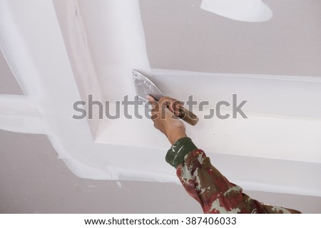 hand of worker using gypsum plaster ceiling joints at construction site - stock photo