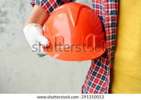 Hand of worker with red hard-hat - stock photo