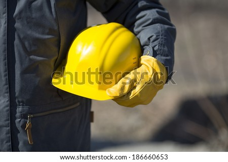 hand of worker with yellow hard-hat,natural light - stock photo