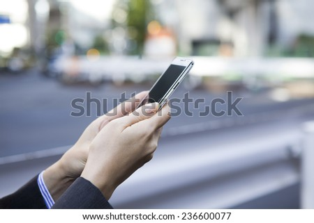 Hand of young business woman with a smart phone - stock photo