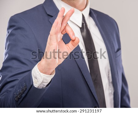 Hand OK sign isolated on gray background. Business success concept. - stock photo