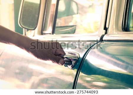 Hand on handle. Close-up of hand's man opening a vintage car door - stock photo