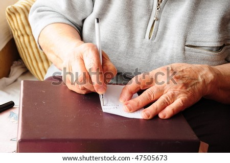 hand on paper writing with a pen - stock photo