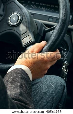 Hand on steering wheel - stock photo