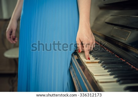 hand on the key of the piano - stock photo