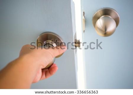 Hand open door knob - stock photo