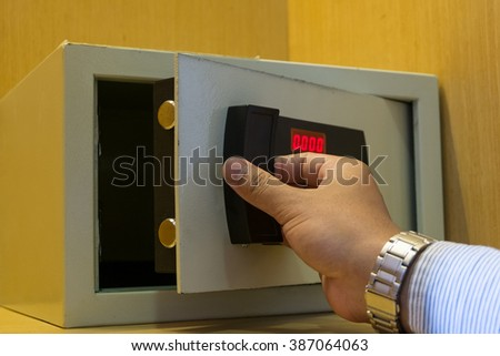 Hand open electronics safe in yellow wardrobe - stock photo