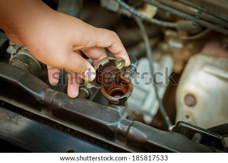 Hand open valve metal cover on an radiator for engine cooling - stock photo
