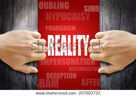 """Hand opening a wooden door found the word """"REALITY"""" in the middle of many different words. - stock photo"""