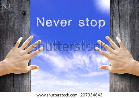 "Hand opening the wooden door and see ""Never Stop"" text cloud in the Sky. - stock photo"
