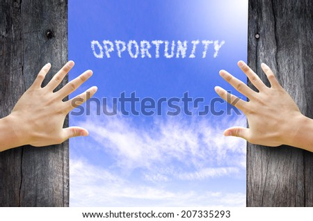 """Hand opening the wooden door and see """"Opportunity"""" text cloud in the Sky. - stock photo"""