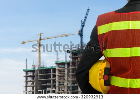 Hand or arm of engineer hold yellow plastic helmet in front of buildings and construction cranes - stock photo