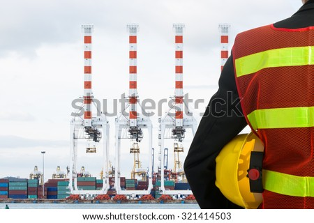 Hand or arm of engineer hold yellow plastic helmet in front of cargo port loading - stock photo