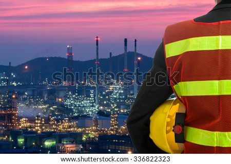 Hand or arm of engineer hold yellow plastic helmet in front of oil refinery industry - stock photo