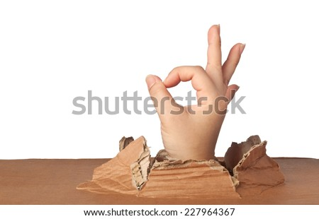 Hand out of a hole showing an okay sign   - stock photo