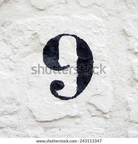 hand painted house number nine. black numeral on a white stucco wall - stock photo