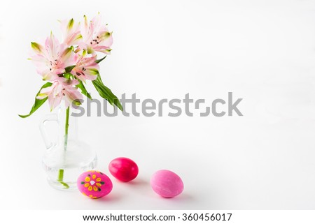 Hand-painted pink Easter eggs with light delicate pink flowers in a glass vase on white background. Easter background. Easter symbol. Top view with copy space. Horizontal - stock photo