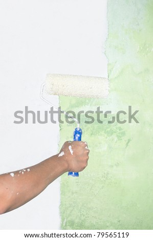 Hand painting on wall with roller - stock photo