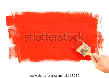 Hand painting the wall with red brush - stock photo