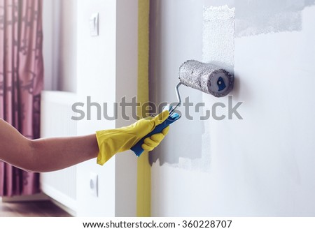 Hand painting wall in apartment - stock photo