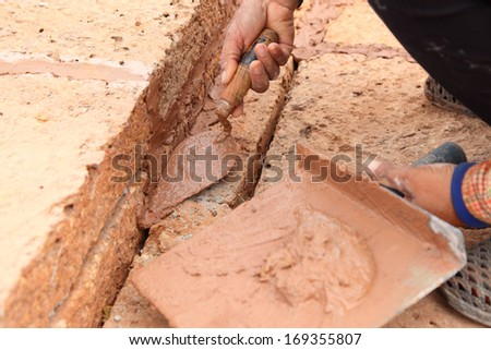 hand pastering cement mortal on the brick wall laterite - stock photo