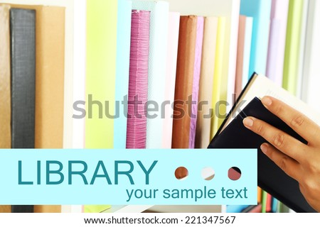 Hand picking book in library - stock photo