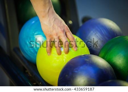 hand picks a bowling ball - stock photo