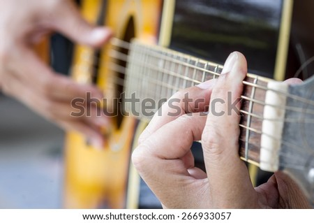 Hand playing acoustic guitar, close up - stock photo
