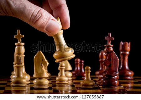 Hand playing wood chess on black background - stock photo