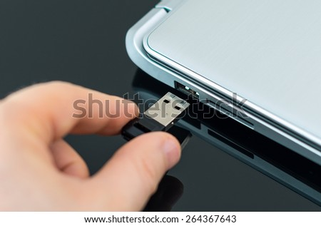 Hand plugging usb flash drive to laptop. - stock photo