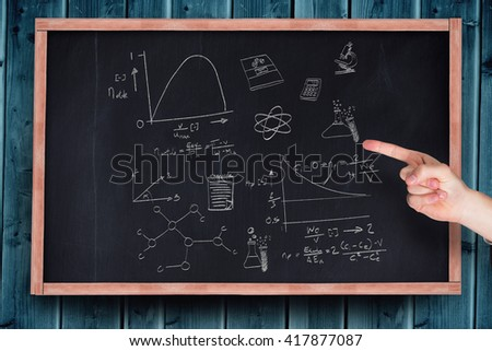 Hand pointing against blackboard with copy space on wooden board - stock photo