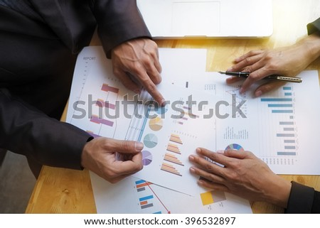 hand pointing at business document during discussion at meeting - stock photo