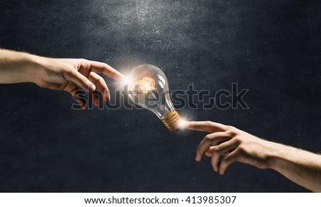 Hand pointing light bulb - stock photo