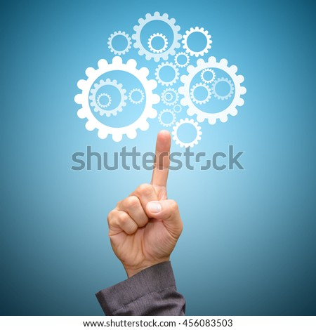 Hand pointing to gear system - stock photo