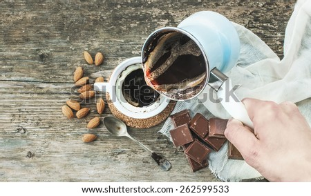 Hand pouring freshly brewed coffee from cezve - coffee pot - to a cup. Roasted almonds, a spoon, a towel, chocolate bar pieces and rough wooden desk at the background. Top view - stock photo