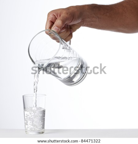 Hand pouring jug with water - stock photo