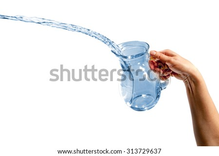 Hand pouring water from glass jug over white background - stock photo