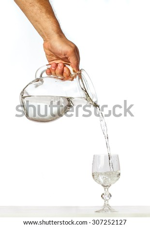 Hand pouring water from glass jug to glass cup on white background - stock photo