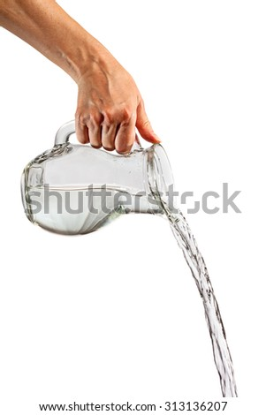 Hand pouring water from glass pitcher over white background - stock photo