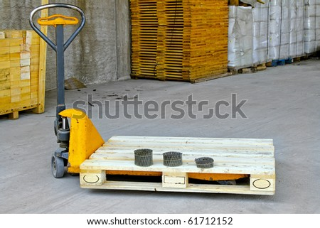 Hand powered pallet jack in wooden warehouse - stock photo